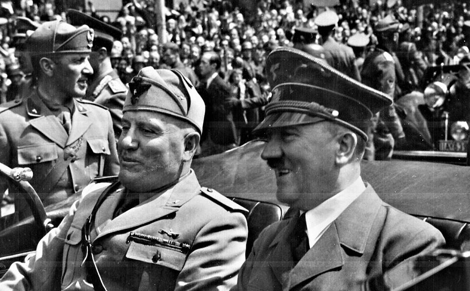 O líder fascista italiano Benito Mussolini no banco de trás de um veículo, acompanhado pelo líder nazista alemão Adolf Hitler, em Munique, 1940